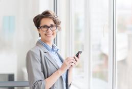 Jonge vrouw met bril in grijs jasje heeft een mobiele telefoon in haar hand en kijkt lachend in de camara.