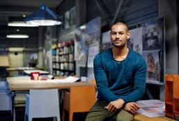 Jonge man zit op en bureau en kijkt blij in de camera. Op de achtergrond een kantoor in bouw of architectuur.