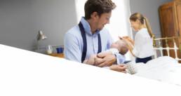 Man in overhemd met losse stropdas houdt baby vast. Op de achtergrond zien we een lachende vrouw.