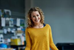 Jonge, blonde vrouw met gele trui kijkt lachtend inde camera. Op de achtergrond een kantoor met bouwtekeningen.