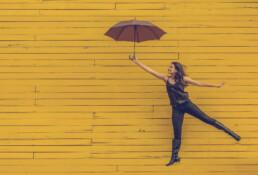 Een voruw die helemaal in het zwart gekleed is houdt een bruine paraplu vast en maakt een sprong. Op de achtergrond zijn gele planken te zien.