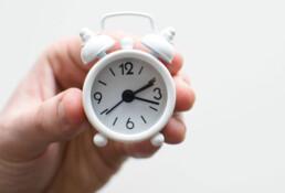 Een hand houdt een klein wit klokje vast. Op de klok is het tien voor half drie.