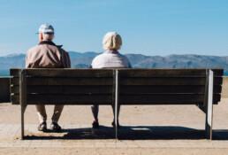 Twee oudere mensen zitten op een bankje en kijken uit over bergen.