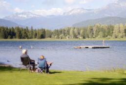 Twee oudere mensen zitten op een klapstoel aan de rand van een meer. Op de achtergrond zijn bergen te zien. het is mooi weer.