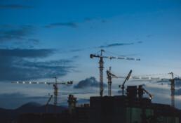 Prachtige donkere lucht, waartegen zich kranen bij een bouwplaats aftekenen.