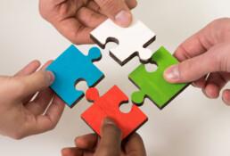 Gekleurde puzzelstukjes met vier handen: de cao-onderhandelingen is best een puzzel