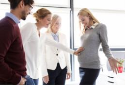 Zwangere vrouw op kantoor met collega's. Collega raakt haar buik aan.